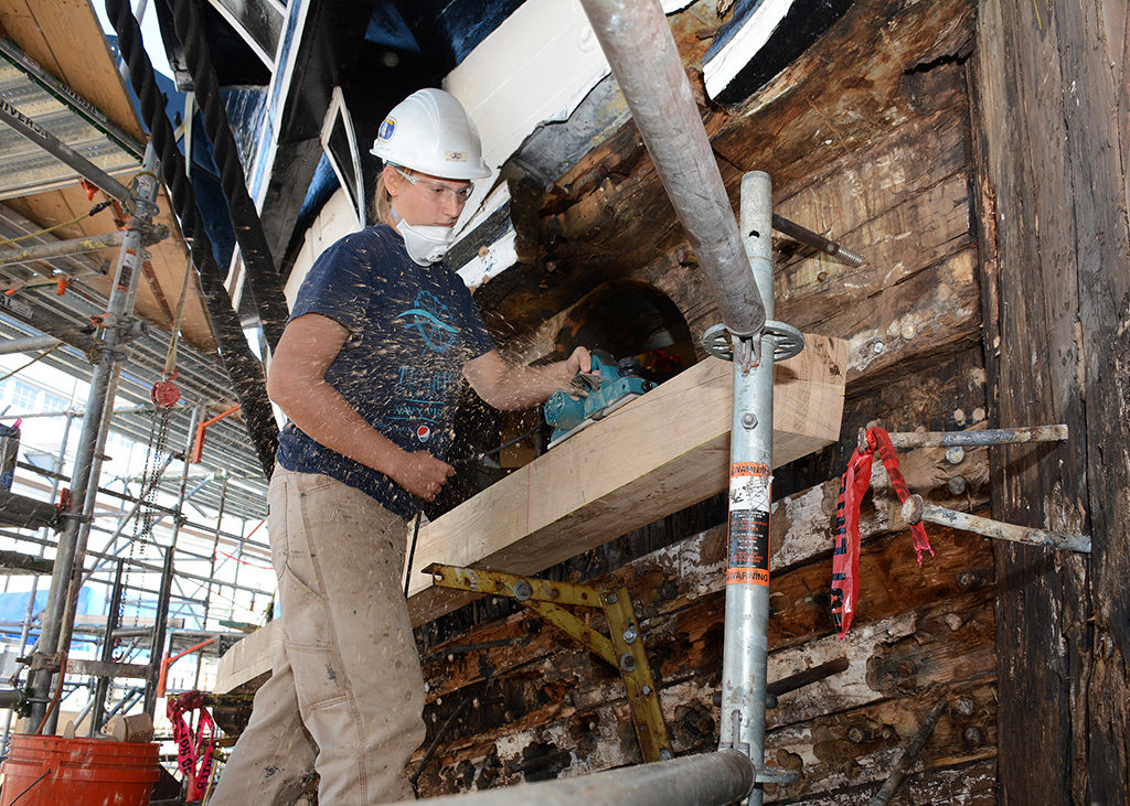 NHHC Detachment Boston ship restorer Kelsey Raver planes a new starboard bow plank. [Courtesy U.S. Navy. Photo by MCSN Victoria Kinney]